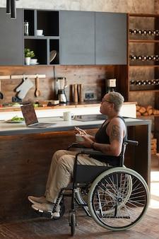 Pionowy portret współczesnej wytatuowanej kobiety na wózku inwalidzkim, oglądającej filmy na laptopie w domu