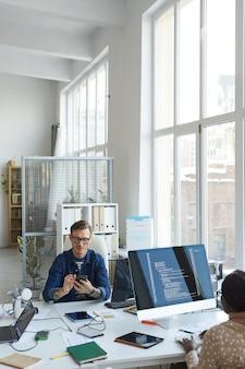 Pionowy portret współczesnych programistów it wykorzystujących komputery do programowania kodu podczas pracy nad oprogramowaniem vr w biurze, kopia przestrzeń