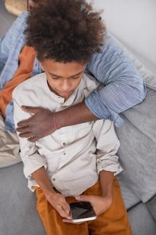 Pionowy portret wysokiego kąta nastoletniego afroamerykańskiego chłopca korzystającego ze smartfona podczas relaksu na kanapie z ojcem