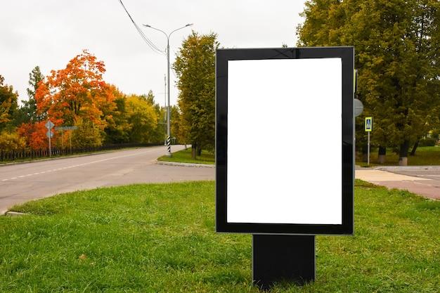 Pionowy pusty billboard na ulicy miasta w jesienny dzień