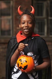 Pionowy średni portret szczęśliwego afroamerykańskiego chłopca przebranego za diabła z czerwonymi rogami trzymającego kosz pełen cukierków po cukierek albo psikus