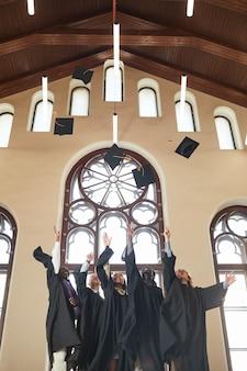 Pionowy szerokokątny widok na trzech młodych ludzi rzucających kapeluszami w powietrze podczas ceremonii ukończenia szkoły w pomieszczeniu w klasycznym audytorium szkolnym, kopia przestrzeń