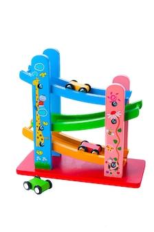 Pionowy tor z samochodami wyścigowymi. materiał to drewno. zabawka edukacyjna montessori. białe tło. zbliżenie.
