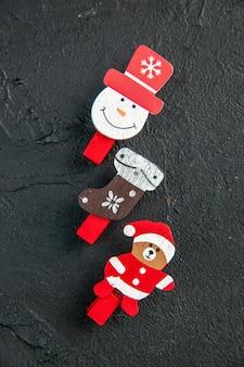 Pionowy widok akcesoriów do dekoracji nowego roku wyłożonych w rzędzie na czarnej powierzchni