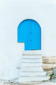 Pionowy widok białych schodów i niebieskich drzwi z nikim. cel podróży letnich w hiszpanii.