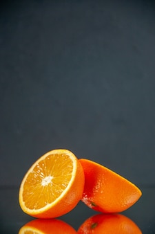 Pionowy widok ciętych świeżych pomarańczy stojących obok siebie na świetle na czarnym tle z wolną przestrzenią