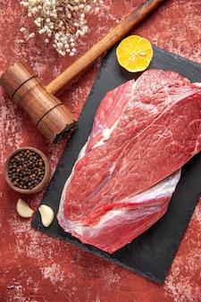 Pionowy widok cytryny czerwonego surowego świeżego mięsa na czarnej desce i brązowej drewnianej papryki młotkowej na pastelowym czerwonym tle