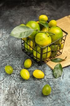 Pionowy widok czarnego kosza ze świeżymi zielonymi mandarynkami i kumkwatami na gazetach na szarym tle