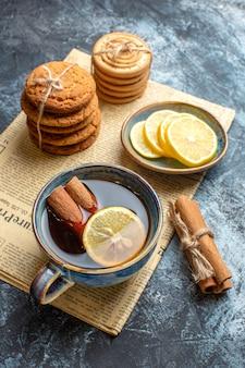 Pionowy widok czasu na herbatę z ułożonymi pysznymi ciasteczkami z cytryną cynamonową na starej gazecie na ciemnym tle
