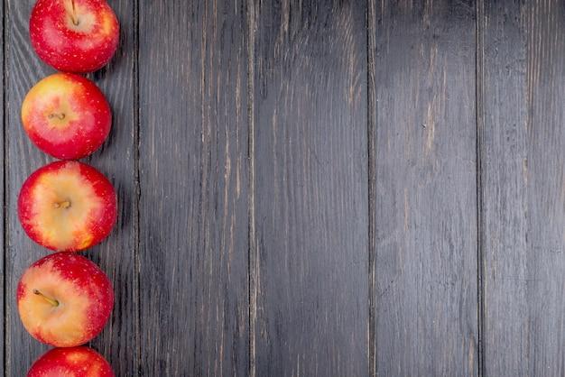 Pionowy widok czerwonych jabłek po lewej stronie i drewniane tła z miejsca na kopię