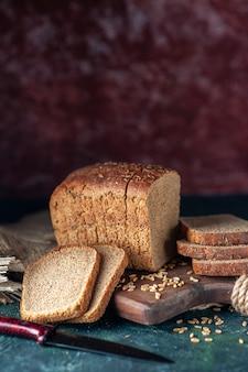 Pionowy widok dietetycznego czarnego chleba pszenicy na drewnianej desce do krojenia nóż kwiat brązowy ręcznik na tle mieszanych kolorów