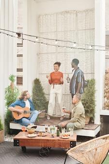 Pionowy widok na całej długości na zróżnicowanej grupie przyjaciół tańczących podczas imprezy plenerowej na dachu, z młodym mężczyzną grającym na gitarze