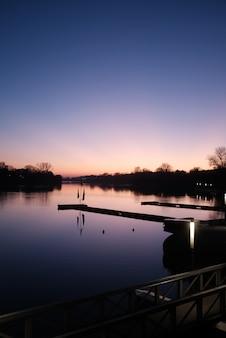 Pionowy widok na spokojną rzekę pod pięknym jasnym niebem o zachodzie słońca