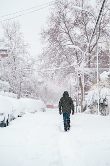 Pionowy widok nierozpoznawalnego podróżnika idącego po środku śniegu.
