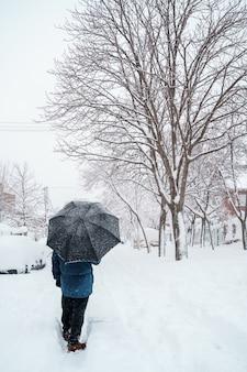Pionowy widok nierozpoznawalnego podróżnika z parasolem pośrodku śniegu.