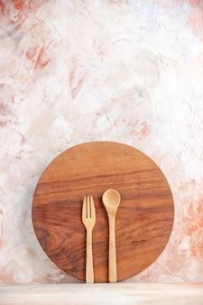 Pionowy widok okrągłej drewnianej deski do krojenia i łyżek stojących na kolorowej powierzchni