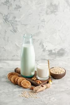 Pionowy widok otwartego szklanego kubka butelki wypełnionego łyżką mleka i płatkami owsianymi w brązowych garnkach na lodowym tle