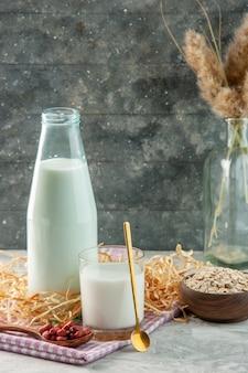 Pionowy widok otwartego szklanego kubka butelki wypełnionego mlekiem i fasolą w łyżce na fioletowym ręczniku w paski