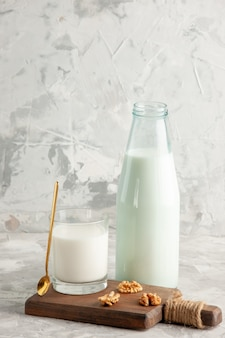 Pionowy widok otwartej szklanej butelki i kubka wypełnionego łyżką do mleka i orzechem włoskim na lodowym tle