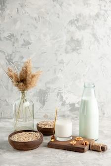 Pionowy widok otwartej szklanej butelki wypełnionej łyżką mleka i owsem orzechowym w brązowym garnku na lodowej ścianie