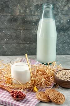 Pionowy widok otwartej szklanej butelki wypełnionej mlekiem i fasolą w łyżkowych ciasteczkach owsianych na fioletowym ręczniku w paski