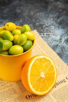 Pionowy widok owoców cytrusowych na gazecie na szarym tle