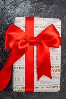 Pionowy widok pięknego pudełka na prezenty wiązanego czerwoną wstążką na lodowatym ciemnym tle