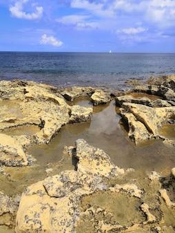 Pionowy widok pięknej plaży ze skałami na malcie uchwyconej w słoneczny dzień