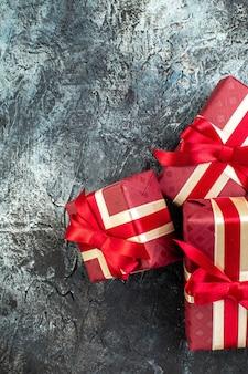 Pionowy widok pięknie zapakowanych pudełek na prezenty w ciemności