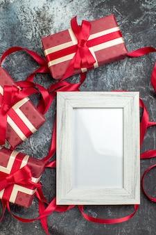 Pionowy widok pięknie zapakowanych pudełek na prezenty związanych wstążką z ramką na zdjęcia na lodzie