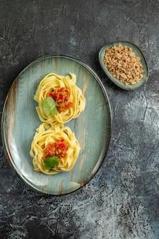 Pionowy widok pysznego makaronu z mięsem pomidorowym i zielenią na niebieskim talerzu na lodowym tle