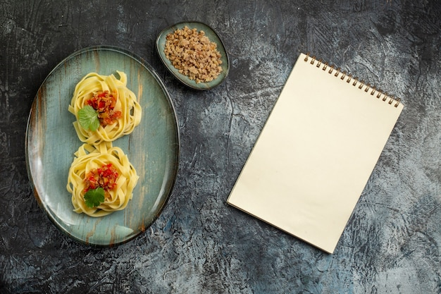 Pionowy widok pysznego makaronu z mięsem pomidorowym i zielenią na niebieskim talerzu obok spiralnego notatnika na lodowym tle