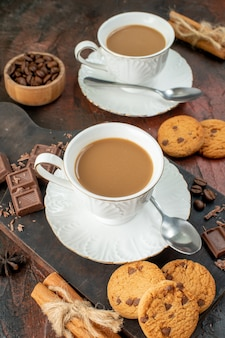 Pionowy widok pysznej kawy w białych filiżankach na drewnianej desce do krojenia ciasteczka cynamonowe limonki batony czekoladowe