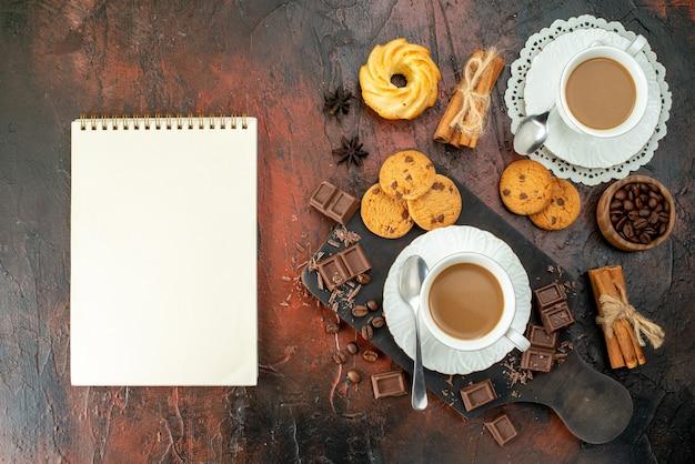 Pionowy widok pysznej kawy w białych filiżankach na drewnianej desce do krojenia ciasteczka cynamonowe limonki czekoladowe batony spiralny notatnik na mieszanym kolorowym tle