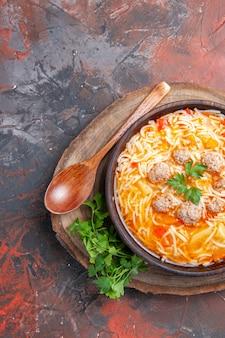 Pionowy widok pysznej zupy z makaronem z kurczakiem na drewnianej desce do krojenia łyżka zieleni na ciemnym tle