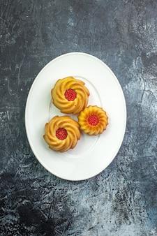 Pionowy widok pysznych ciastek na białym talerzu na ciemnej powierzchni