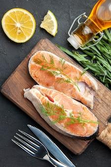 Pionowy widok ryby łososia na brązowej drewnianej desce do krojenia z zielonymi plasterkami cytryny opadła butelka oleju po prawej stronie na ciemnym stole