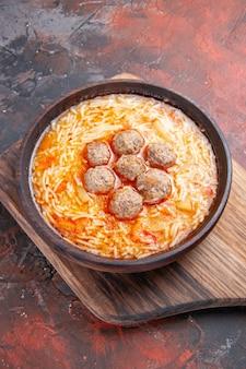 Pionowy widok smacznej zupy z klopsikami z makaronem na drewnianej desce do krojenia na ciemnym tle