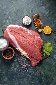 Pionowy widok świeżego surowego czerwonego mięsa na czarnej tacy pieprzowej butelce z olejem cytrynowym na ciemnym tle