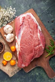 Pionowy widok świeżych surowych czerwonych mięs zielony czosnek na brązowej drewnianej desce do krojenia pomidory pieprz na nagim kolorze nóż do ręczników na ciemnym tle