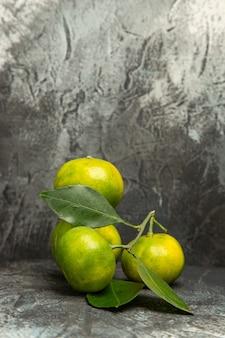 Pionowy widok świeżych zielonych mandarynek z liśćmi na szarym tle materiału