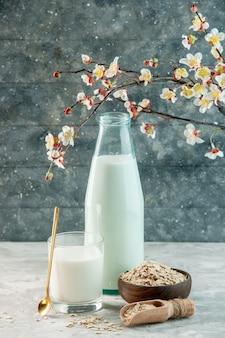 Pionowy widok szklanego kubka i butelki wypełnionej mlekiem i owsem wewnątrz poza brązowym kwiatem doniczkowym na szarym tle