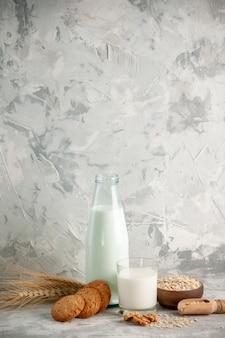 Pionowy widok szklanej butelki i kubka wypełnionego mlekiem na drewnianej tacy i ciasteczkach, łyżkach owsa w brązowym garnku na białym stole na lodowym tle