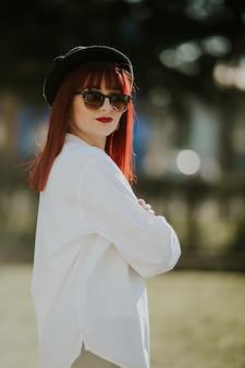 Pionowy widok z boku młodej uśmiechniętej kobiety z rudymi włosami, okularami przeciwsłonecznymi i kapeluszem pozującej w parku