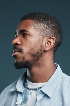Pionowy widok z boku portret przystojnego afrykańskiego mężczyzny przeciw niebieskiemu skupieniu na zarysie profilu
