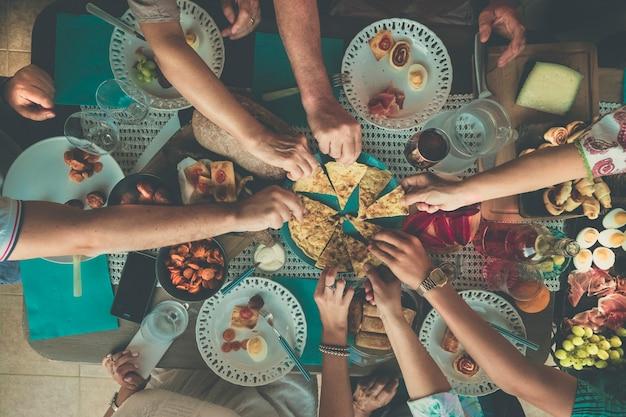 Pionowy widok z góry na grupę przyjaciół cieszących się razem jedzeniem i kolacją, jedzącą i zabierającą z naczyń?