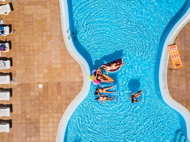 Pionowy widok z lotu ptaka grupy przyjaciółek bawią się razem podczas letnich wakacji w basenie z kolorowymi pontonami lilos na niebieskiej wodzie
