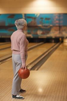 Pionowy widok z tyłu portret białowłosej starszej kobiety grającej w kręgle i odwracającej wzrok, stojąc przy pasie trzymając piłkę