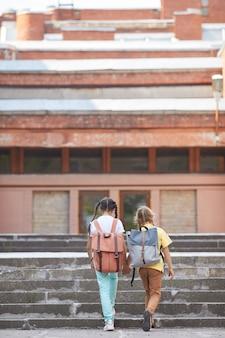 Pionowy widok z tyłu portret dwóch sióstr idących do szkoły z plecakami podczas chodzenia po schodach do dużego budynku, miejsce na kopię