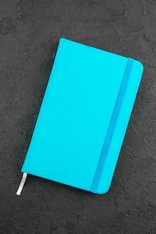 Pionowy widok zamkniętego niebieskiego notatnika na czarno